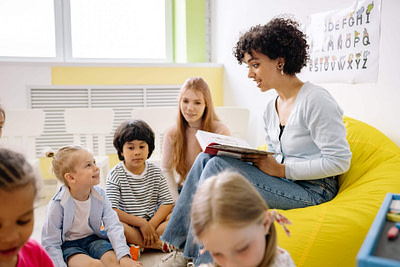 woman reading a book to the children