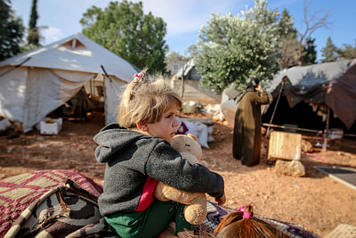 cute girl with toy in refugee camp