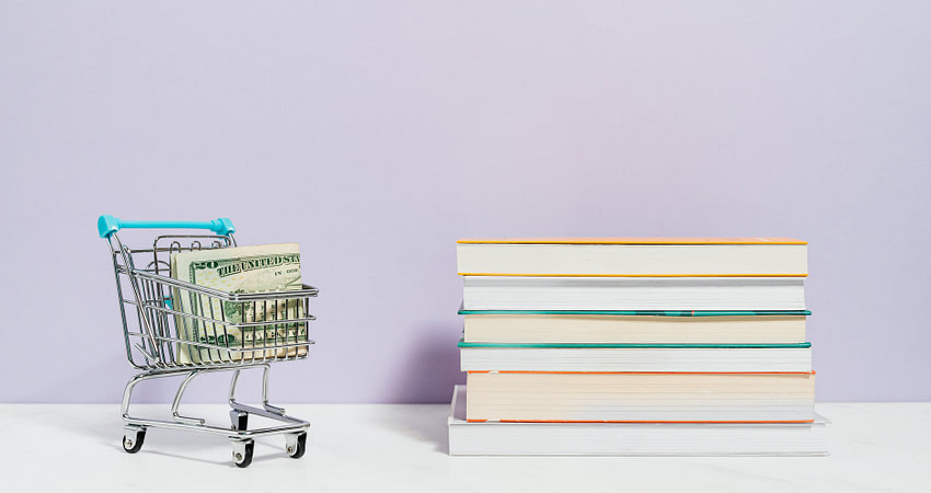 stack of books beside a shopping cart with cash money