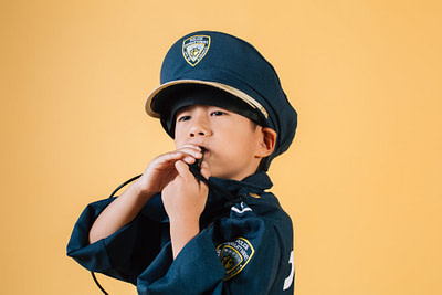 confident ethnic child in police uniform blowing whistle