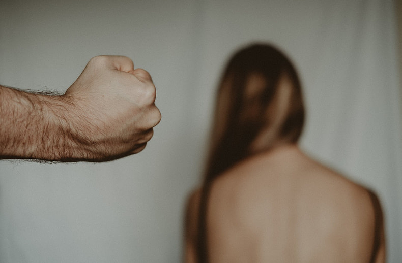 crop man showing fist near anonymous woman