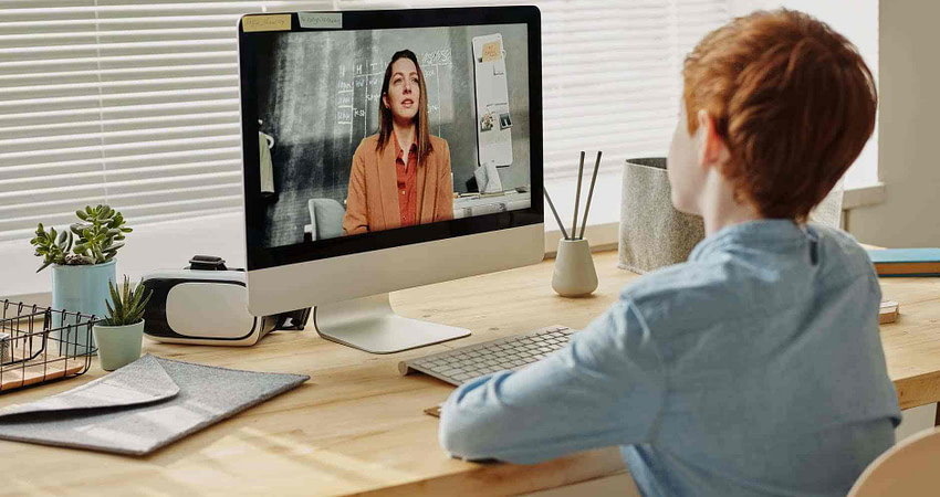 photo of child sitting by the table while looking at the imac