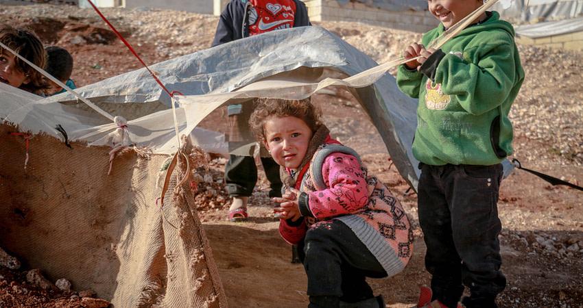 poor ethnic children playing in yard of village